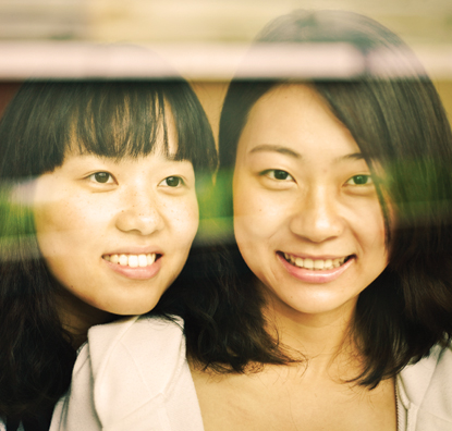 Two women smiling and looking outside a window