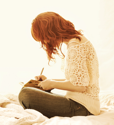 A woman sitting on a bed writing in a journal
