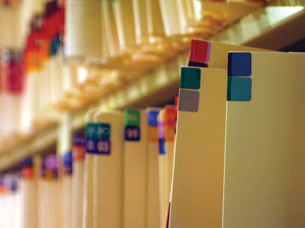 Two office shelves filled with cream, color-coded folders