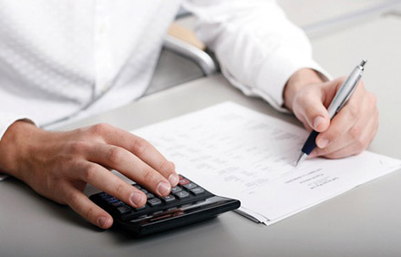 A man's hands using a calculator and holding a pen while reviewing a document