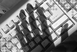 Photo of a shadow of a hand on top of a computer keyboard